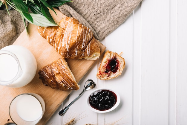 Overhead view of croissant stuffed with berries jam and glass of milk on the table