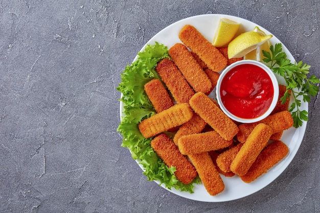 Overhead view of crumbed fish sticks served on a white plate with lemon, lettuce leaves and tomato sauce, view from above, flat lay, close-up