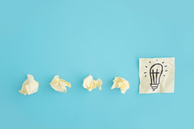 Overhead view of crumpled papers with light bulb draw on the sticky note over the blue background