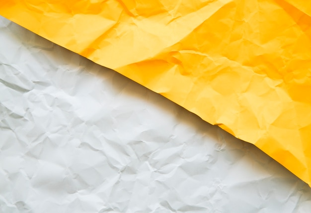 Overhead view of crumpled white and yellow papers