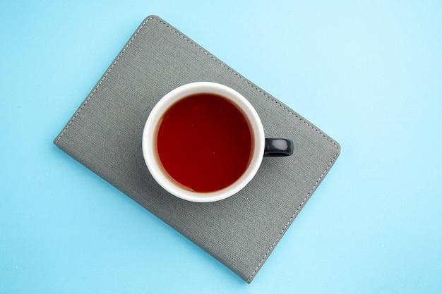 Vista dall'alto di una tazza di tè nero su un taccuino grigio su superficie blu