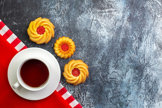 Overhead view of a cup of black tea on a red towel and biscuits on the right side on dark surface