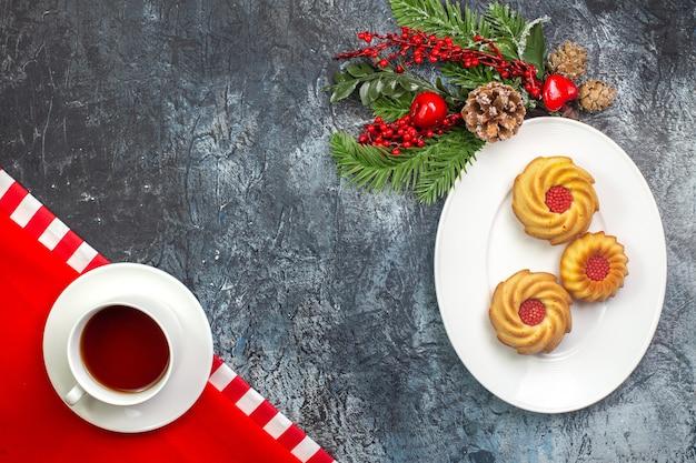 Vista dall'alto di una tazza di tè nero su un asciugamano rosso e biscotti su un piatto bianco accessori di capodanno su superficie scura