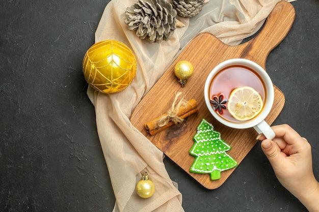 Vista dall'alto di una tazza di tè nero con limone e cannella, accessori per la decorazione del nuovo anno su tagliere di legno