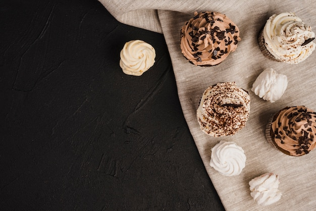 Overhead view of cupcakes and whipped creams on cloth