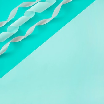 Overhead view of curled satin ribbon on dual background