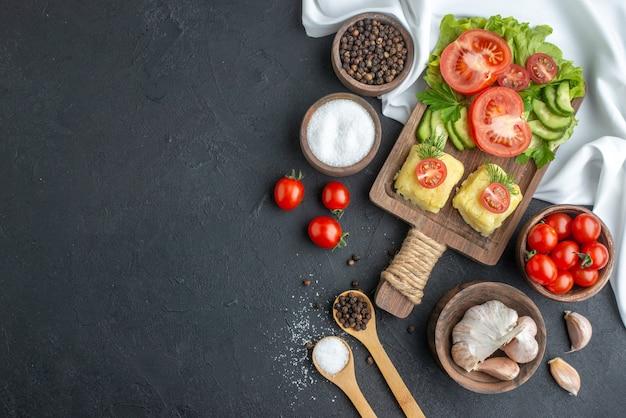 Vista dall'alto di pomodori freschi interi tagliati e formaggio di cetrioli su tavola di legno posate spezie in cucchiai su superficie nera