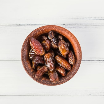 An overhead view of dates in a wooden bowl on white wooden table