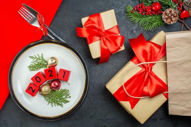 Vista dall'alto di accessori di decorazione numeri su un piatto e bellissimi regali rami di abete cono di conifere su un tavolo scuro