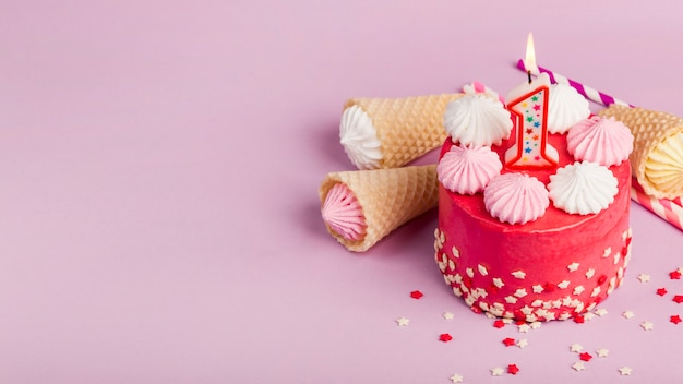 An overhead view of decorative red cakes with waffles cones and aalaw on pink backdrop