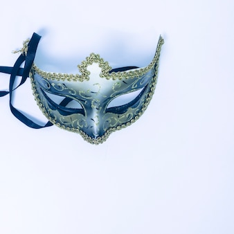 An overhead view of decorative venetian mask on white backdrop