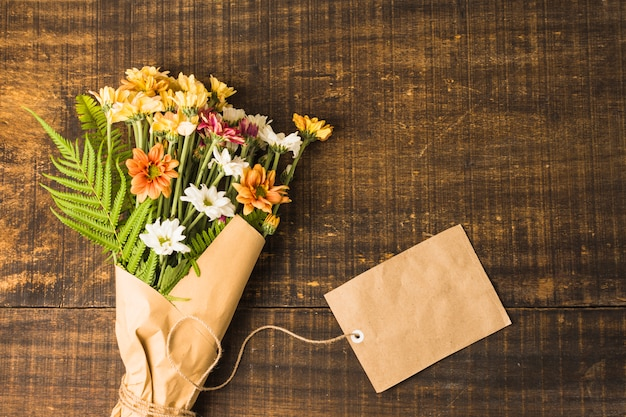 Overhead view of delicate flower bunch and brown paper tag on wooden surface
