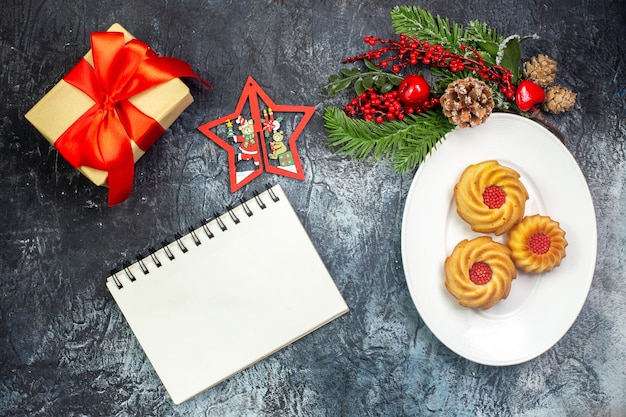 Overhead view of delicious biscuits on a white plate and new year decorations gift with red ribbon next to notebook on dark surface