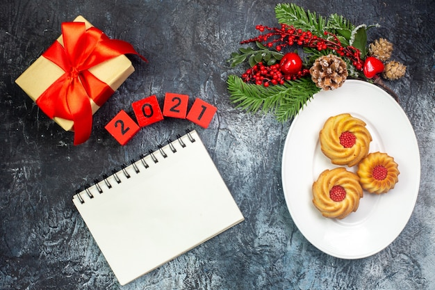 Overhead view of delicious biscuits on a white plate and new year decorations gift with red ribbon next to notebook numbers on dark surface