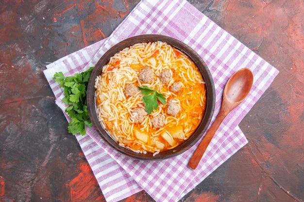 Vista dall'alto di una deliziosa zuppa di pollo con noodles verdi e cucchiaio su un asciugamano spogliato rosa su sfondo scuro