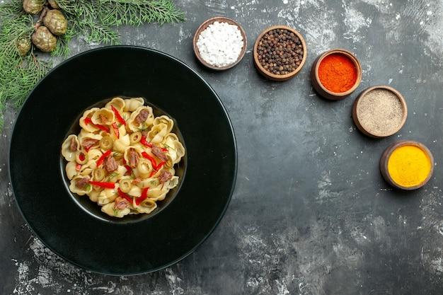 Vista dall'alto di deliziose conchiglie con verdure e verdure su un piatto e un coltello e diverse spezie su sfondo grigio