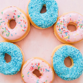 Overhead view of delicious donuts on pink backdrop