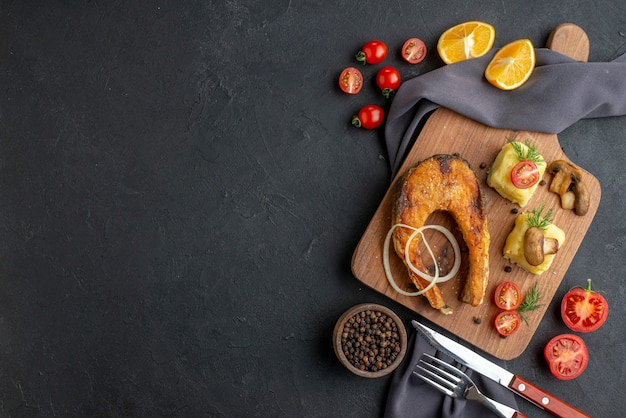 Overhead view of delicious fried fish meal with mushrooms tomatoes cheese on wooden board lemon slices pepper on dark color towel cutlery set pepper on the left side on black distressed surface