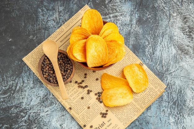 Vista dall'alto di deliziose patatine fatte in casa e ciotola di pepe con il cucchiaio sul giornale sul tavolo grigio