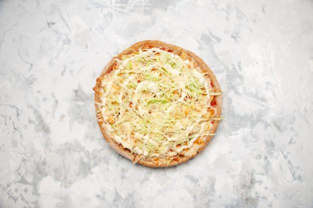 Vista dall'alto di una deliziosa pizza vegana fatta in casa su una superficie bianca macchiata con spazio libero