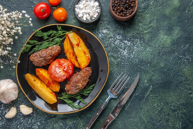 Overhead view of delicious meat cutlets baked with potatoes and tomatoes on a black plate cutlery set white flowers spices garlics on green black mixed colors background