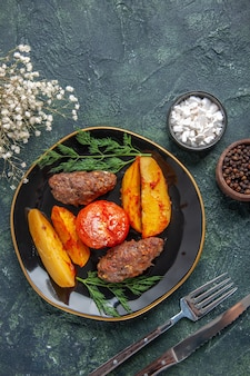 Overhead view of delicious meat cutlets baked with potatoes and tomatoes on a black plate cutlery set white flowers spices on green black mixed colors background