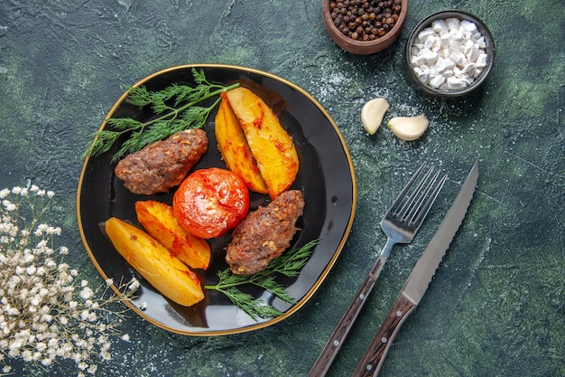 Overhead view of delicious meat cutlets baked with potatoes and tomatoes on a black plate garlics spices cutlery set on green black mix colors background