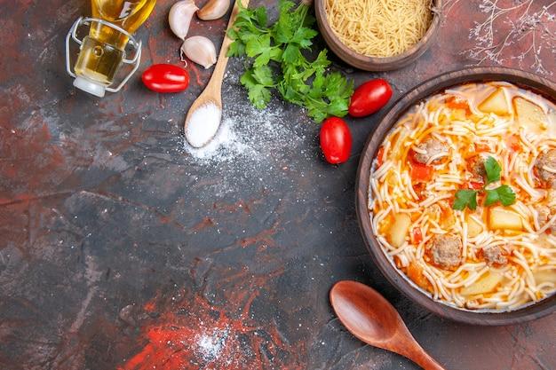 Vista dall'alto di una deliziosa zuppa di noodle con pollo e pasta cruda in una piccola ciotola marrone e cucchiaio di pomodori e verdure all'aglio sullo sfondo scuro