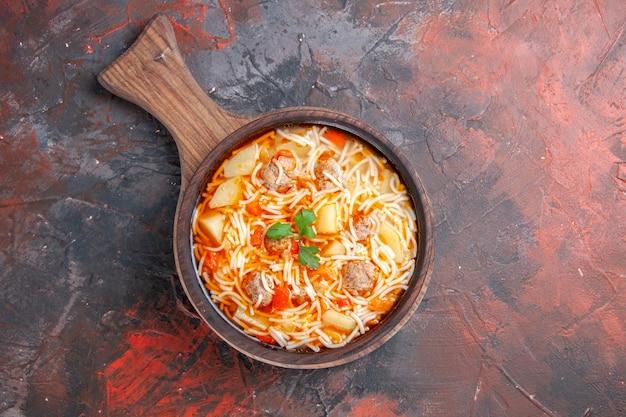 Vista dall'alto di una deliziosa zuppa di noodle con pollo su tagliere di legno su sfondo scuro immagine stock