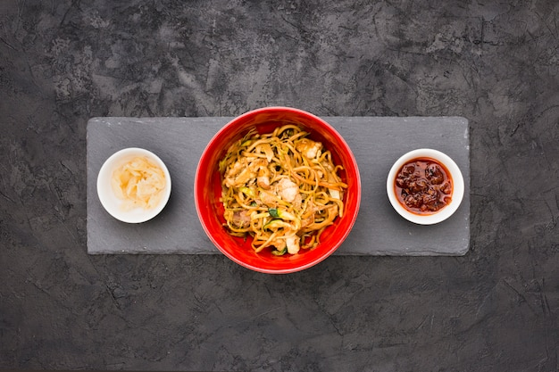 An overhead view of delicious noodles in bowl with sauce and marinated ginger over black slate stone