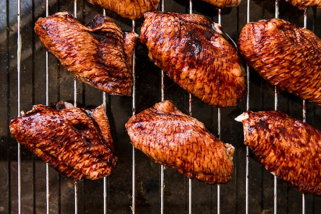 An overhead view of delicious pieces of chicken meat on metal grill