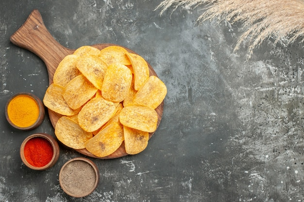 Overhead view of delicious potato chips spices with ketchup on gray table