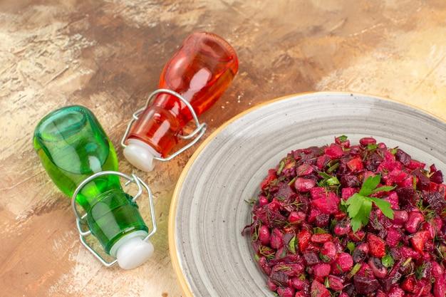 Vista dall'alto di una deliziosa insalata con barbabietola e fagioli e caduta di due bottiglie di olio su sfondo a colori misti