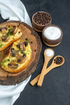 Overhead view of delicious snack with mushrooms on wooden board and spices on white towel on black background