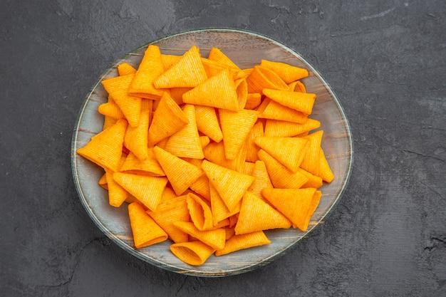Vista dall'alto di deliziosi snack in una ciotola blu su sfondo scuro on