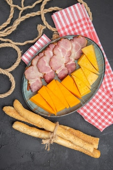 Overhead view of delicious snacks on a blue plate and rope on a black plate