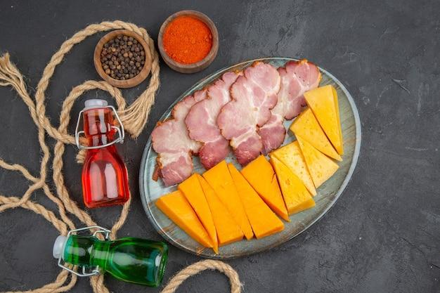 Vista dall'alto di deliziosi snack bottiglie cadute peperoni su asciugamano e corda su sfondo nero