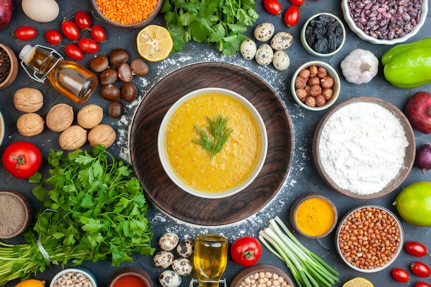 Overhead view of delicious soup and spices in bowl oil vegetables food rustic black wooden table