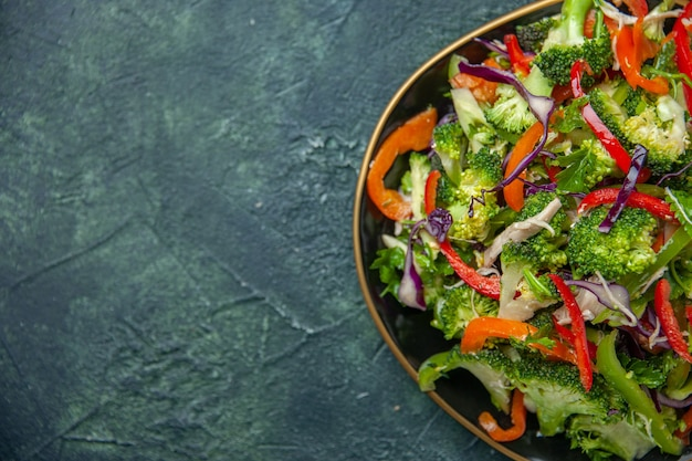 Vista dall'alto di una deliziosa insalata vegana in un piatto con varie verdure fresche sul lato sinistro su sfondo scuro con spazio libero