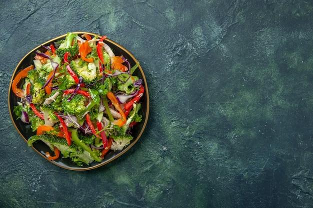 Vista dall'alto di una deliziosa insalata vegana in un piatto con varie verdure fresche sul lato destro su sfondo scuro