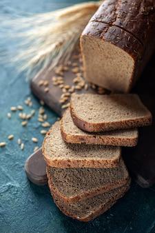Vista dall'alto del pane nero dietetico picchi di grano su tagliere di legno su sfondo blu scuro colori