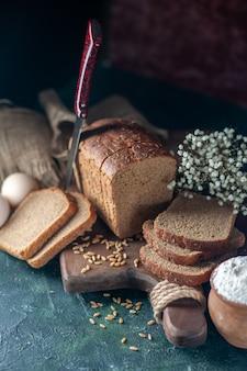 Vista dall'alto dei grani di pane nero dietetico su tagliere di legno coltello fiore uova farina in una ciotola asciugamano marrone su sfondo di colori misti