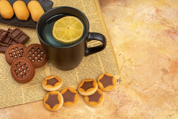 Overhead view of different biscuits and tea in a black cup on mixed color table