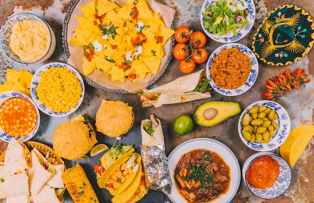 Overhead view of different delicious mexican dishes on rusty background