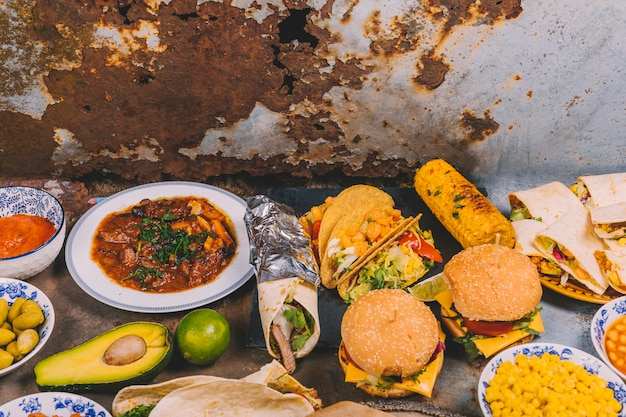Overhead view of different mexican dishes on old metal background