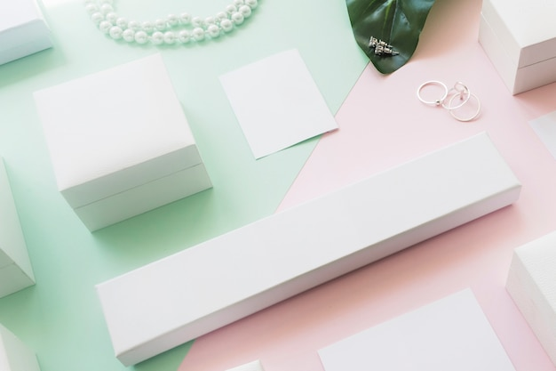 Overhead view of different white boxes on two green and pink paper backdrop