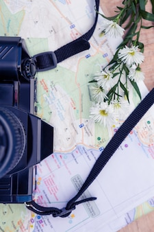 Overhead view of digital camera and map and flowers on table