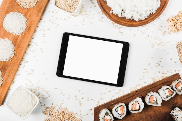 An overhead view of digital tablet surrounded with sushi and variety of uncooked rice
