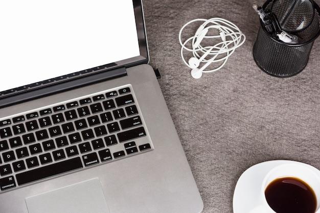 Una vista dall'alto della tavoletta digitale con caffè; auricolari e portapenne su una scrivania grigia