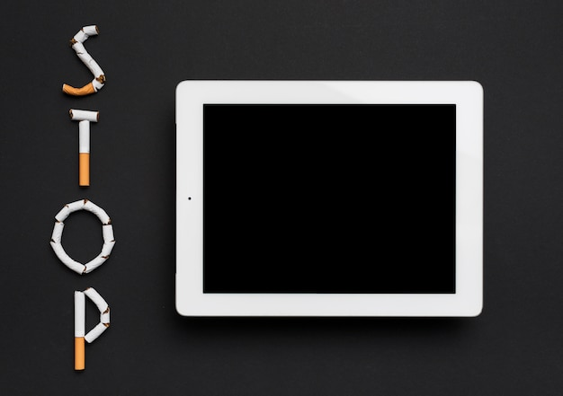 Overhead view of digital tablet with stop word made from cigarette against black background